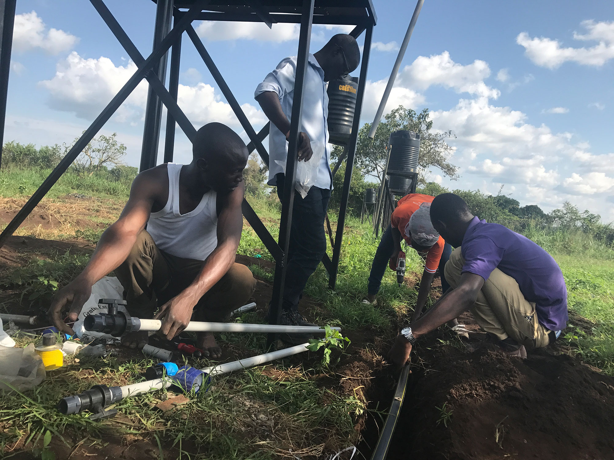 Students help to place pipe in the ground for the irrigation system