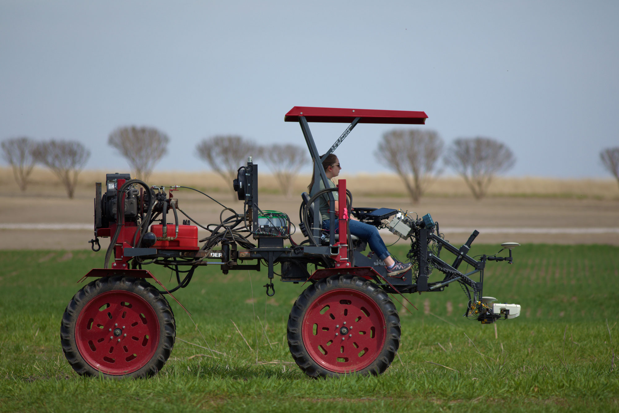 April Mueller, research assistant, drives a specially designed tractor called the Spider