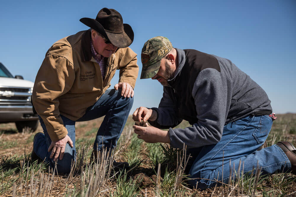 Noble consultant, Jim Johnson, inspects a clump of soil with a rancher.