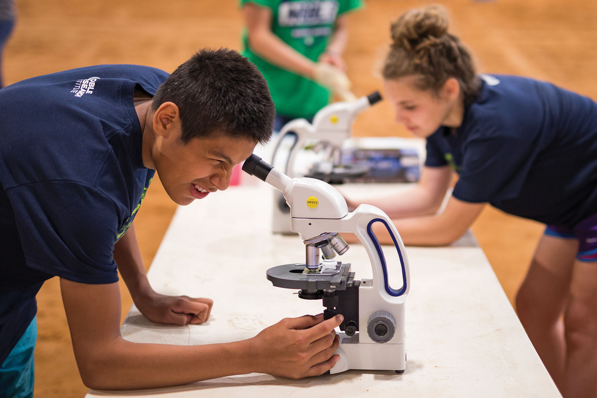 Teens look through microscopes.