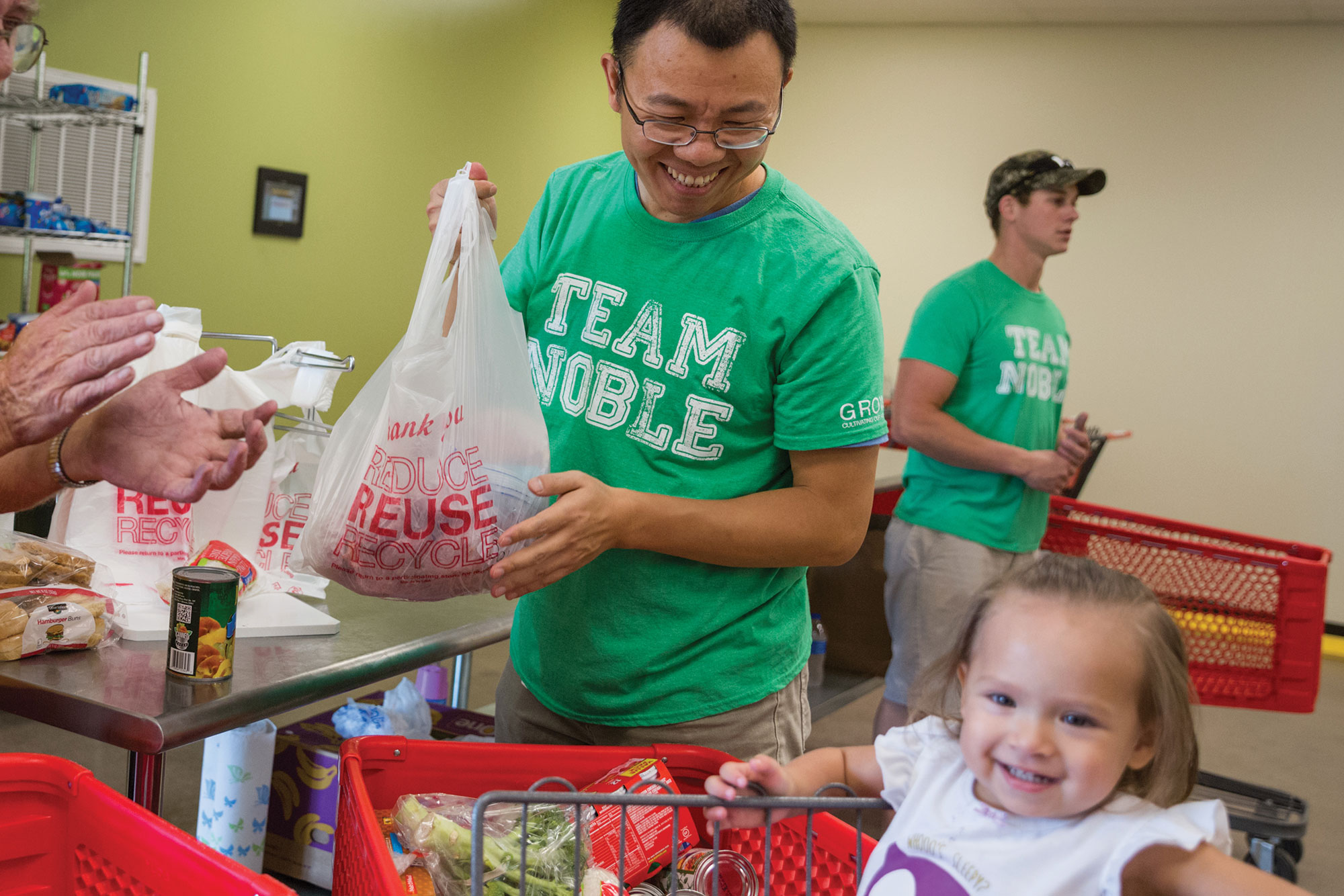 Maofeng Chai, Ph.D. and Landon Riggle help families shop and bag their food selections to take home.