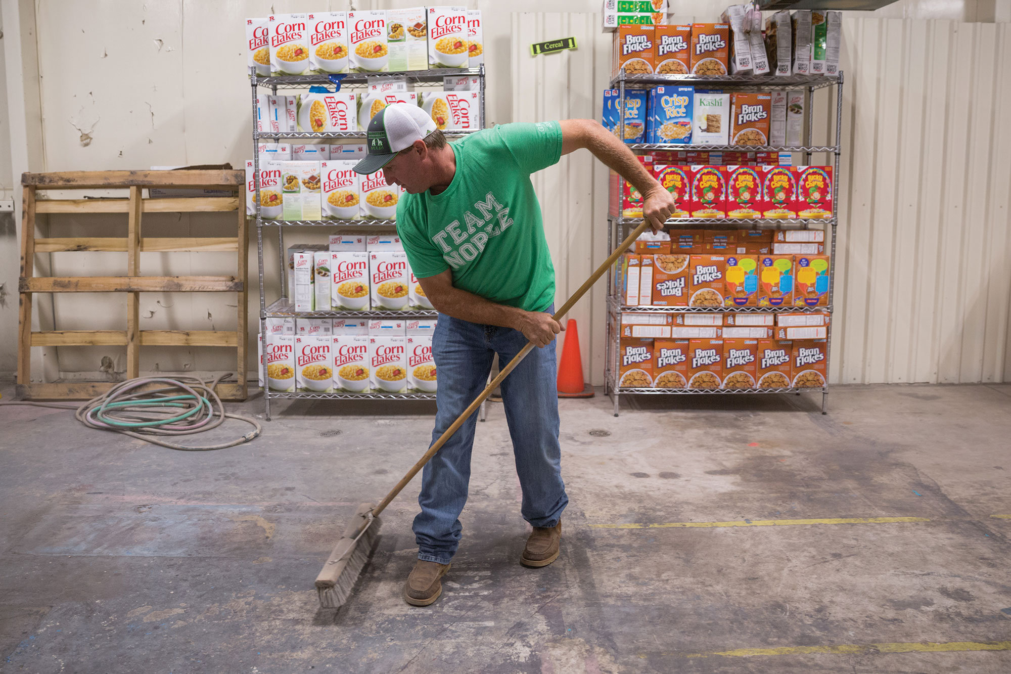 Ronald Trett sweeping the warehouse.