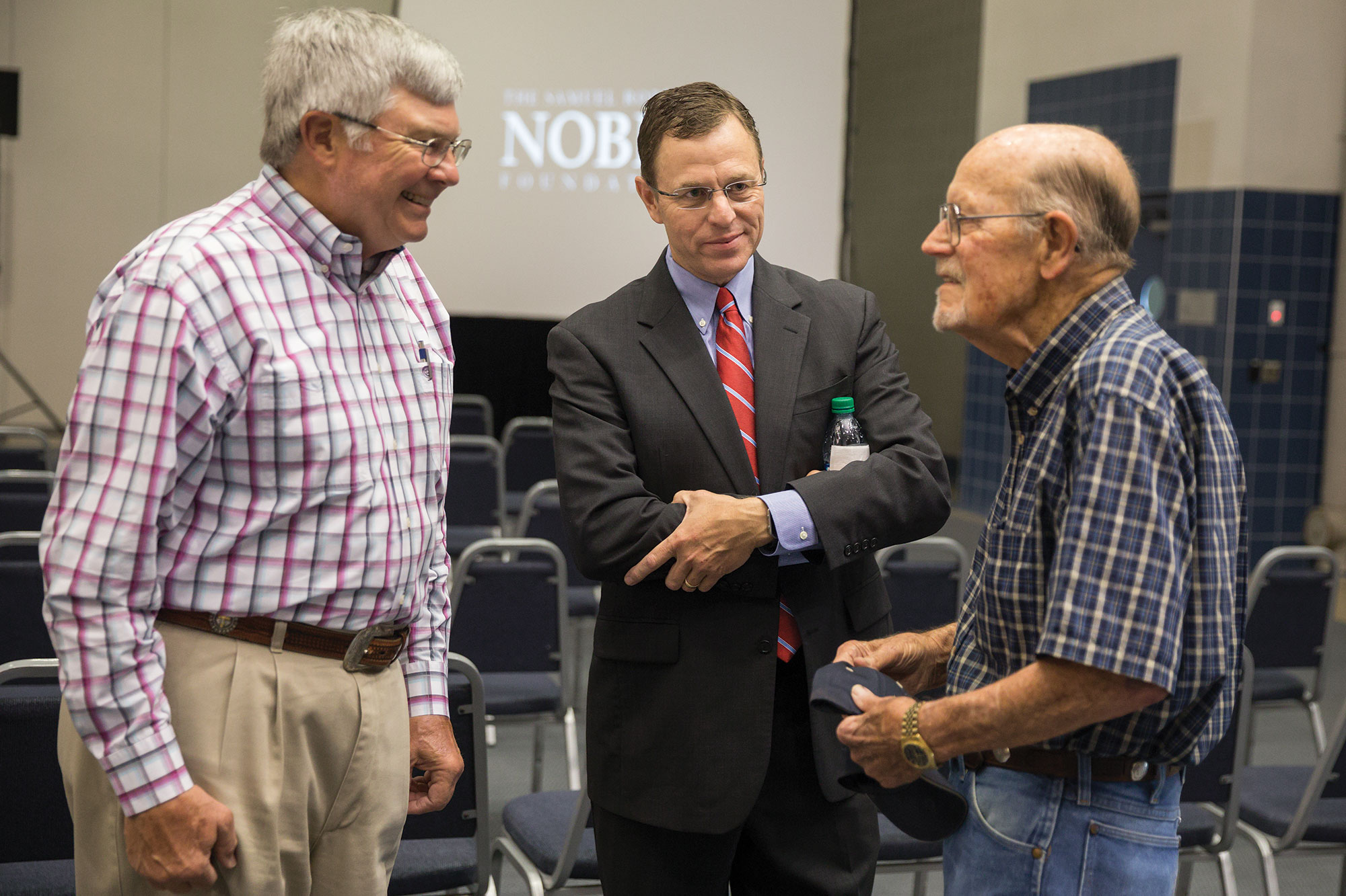 Steve Rhines (center) listens to Noble retirees Fred Schmedt (left) and Gary Simmons following the announcement that the Noble Foundation would be renamed as the Noble Research Institute.
