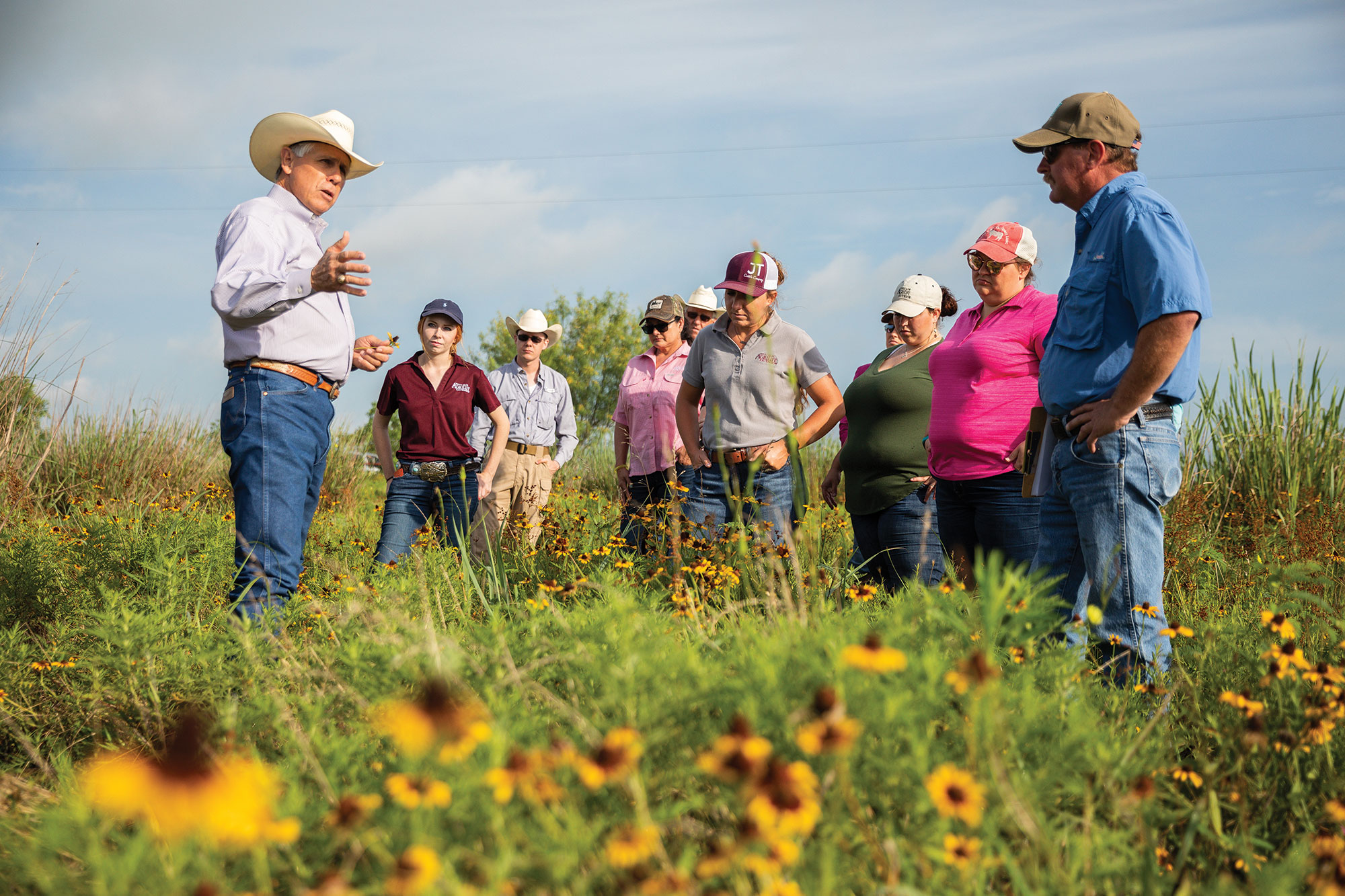 Gary Price (left) discusses soil microbes, water quality and broader beef industry challenges with county extension agents during a tour of his ranch.