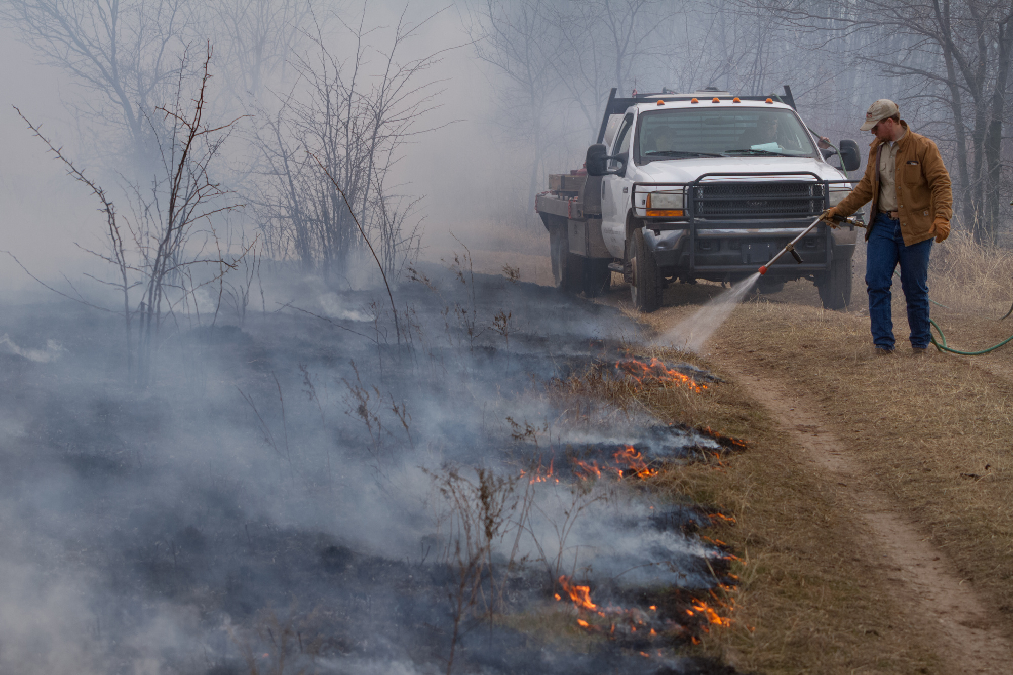 Ag Consultant spraying water at a controlled burn site.